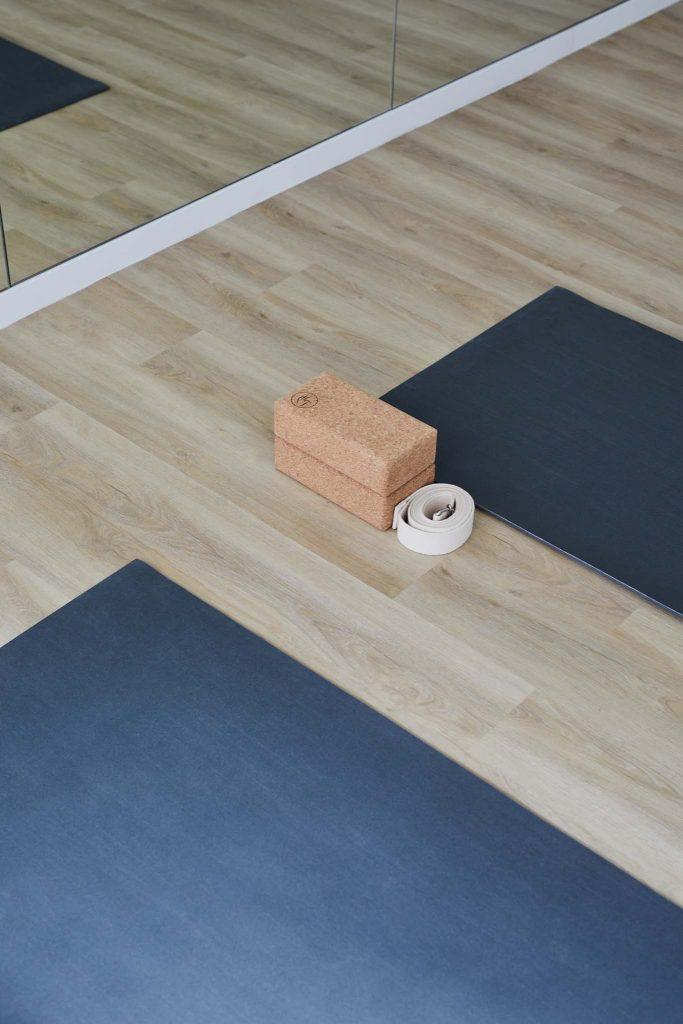 Deux tapis de yoga, une sangle et deux briques de yoga sont posés par terre devant un miroir, dans un studio de yoga à Paris