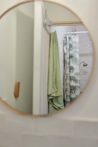 Douche au studio de yoga à Paris reflet dans un miroir doré, serviette posée sur la porte de la douche