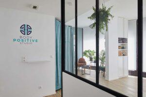 Vue de l'entrée du Studio de yoga à Paris verrière rideaux verts