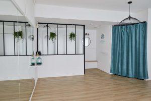 Espace de cours du studio de yoga à Paris grand miroir verrière plantes rideaux verts