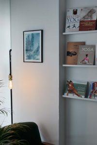 Coin lecture du salon du studio de yoga à Paris une lampe rétro éclaire un mur blanc avec une photographie de feuille de palmier, des livres de yoga sont posés sur des étagères