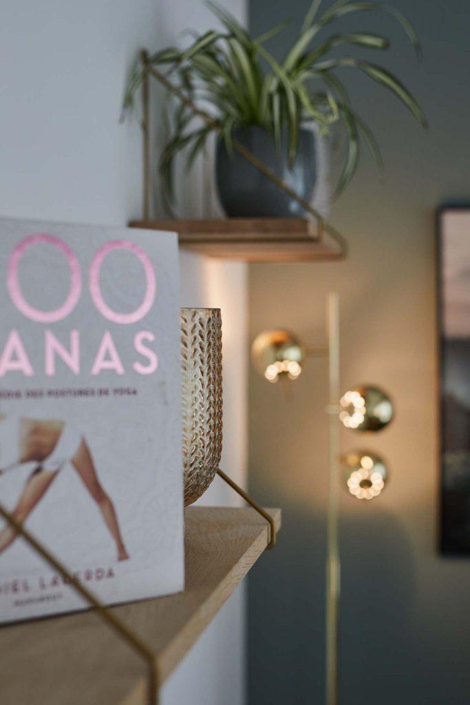 un livre de yoga et une plante posées sur des étagères, un lampadaire doré éclaire un mur, ambiance chaleureuse