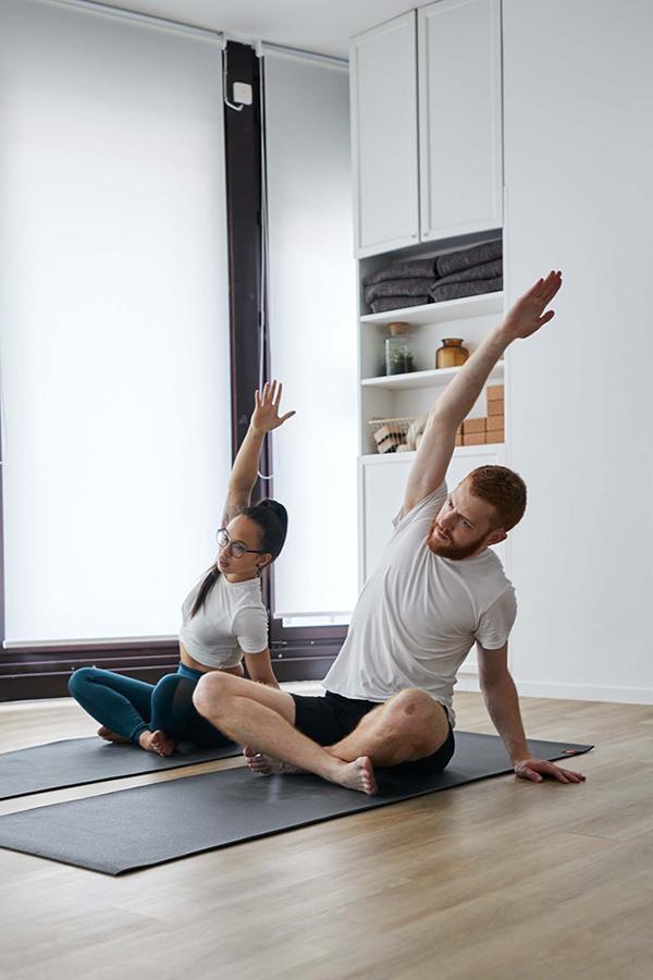 Deux personnes assises sur un tapis de yoga prennent un cours de yoga à Paris un homme une femme font des étirements