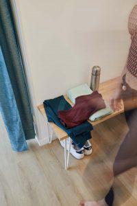 Espace vestiaire du studio de yoga à Paris, vêtements de sport leggings basket gourde serviette posés sur un banc en bois, une personne qui se change passe, rideaux verts décoration soignée