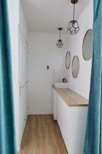Espace vestiaire du studio de yoga à Paris lavabo miroirs portes douche toilettes wc rideaux verts décoration soignée