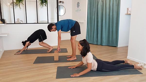 trois personnes sur des tapis de yoga prennent un cours de yoga à Paris deux hommes une femme chien tête en bas cobra pince debout uttanasana adho mukha svanasana bhujangasana