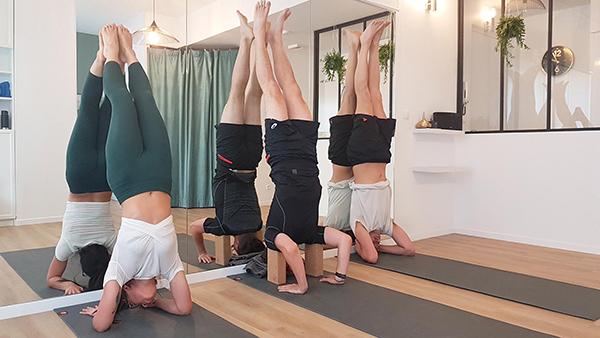 trois personnes sur des tapis suivent une classe d'inversion une femme deux hommes équilibre poirier débutant hatha cirque gymnastique pincha mayurasana sirsasana