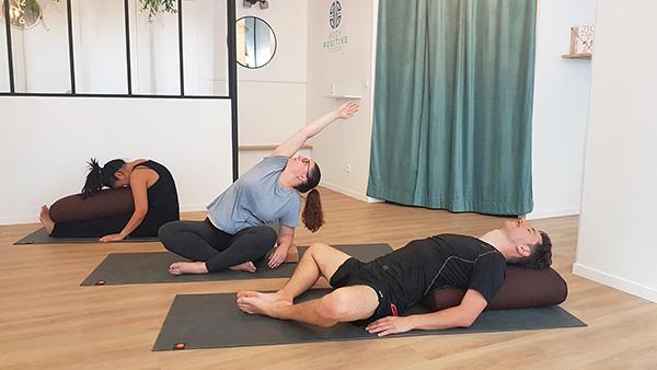 trois personnes sur des tapis de yoga prennent un cours de yoga à paris deux femmes un homme relaxation yoga doux méditation paschimotanasana supta baddha konasana